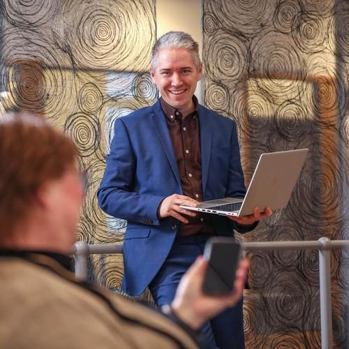 Bild på Christian Kromnér som står med sin laptop öppen. Carin syns i förgrunden med sin mobiltelefon.