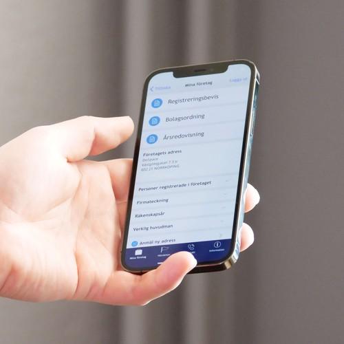 En hand som håller i en smartphone. Bolagsverkets app syns på skärmen