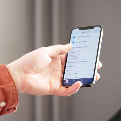 Hand som håller en smartphone. På skärmen visas Bolagsverkets app.