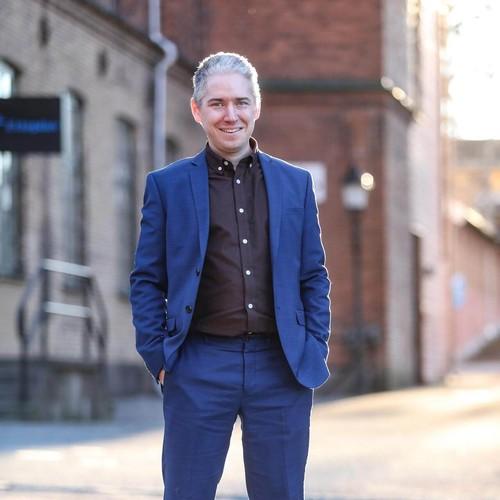 Christian Kromnér i helkroppsporträtt fotograferad på gatan utanför kontoret.